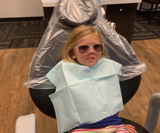 Little girl in dental chair before treatment