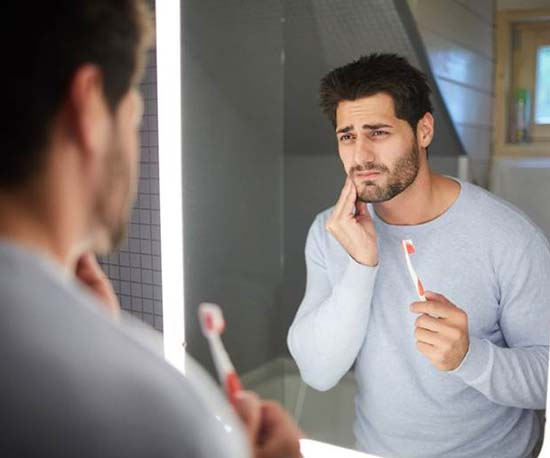 Man with toothbrush holding cheek in pain