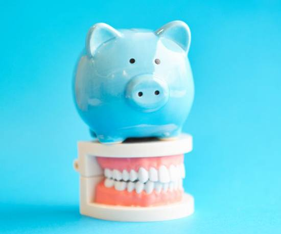 blue piggy bank sitting atop set of full dentures against light blue background
