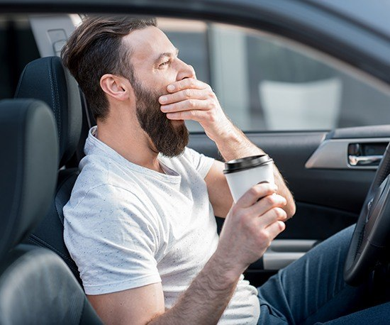 Man in car covering his mouth as he yawns