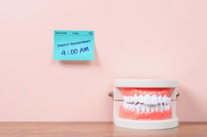 a sticky note with a dental checkup appointment reminder and a model of teeth next to it